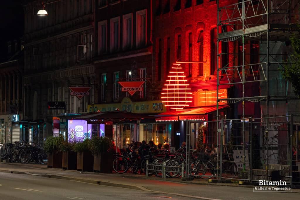 Foto er taget uden diffusionsfilter og der ses en cafe facade med et stort rødt neonskilt en sen aften.