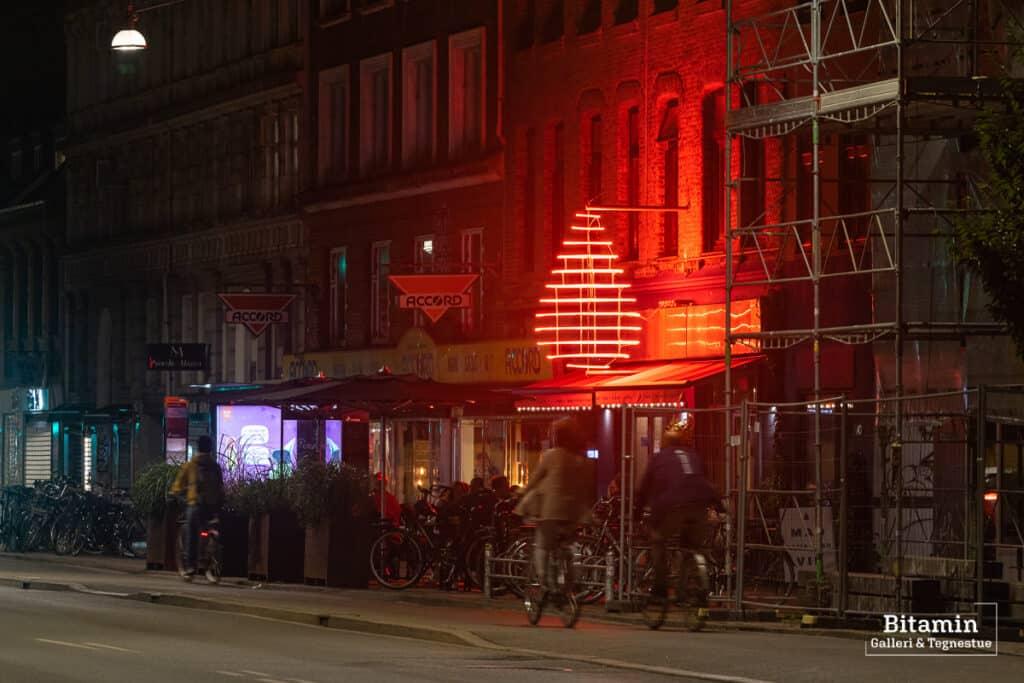 Foto er taget med sort diffusionsfilter og der ses en cafe facade med et stort rødt neonskilt en sen aften. Lyset om neoskiltet bløder ud i billedet