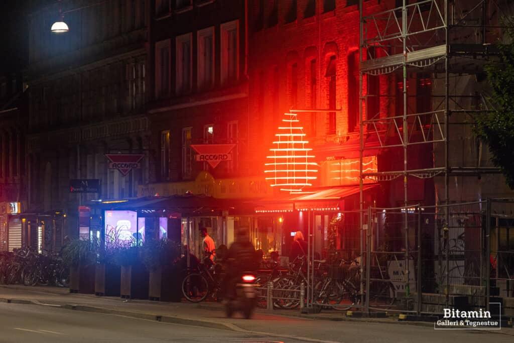 Foto er taget med Allure diffusionsfilter og der ses en cafe facade med et stort rødt neonskilt en sen aften. Lyset om neoskiltet bløder voldsomt ud i billedet
